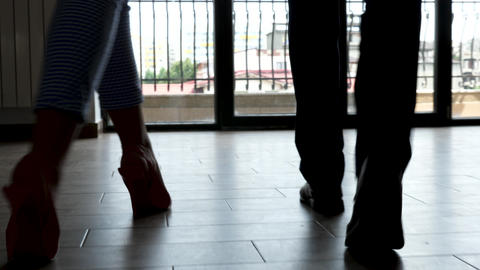Feet in silhouette of businessman and businesswoman walking through the office Footage