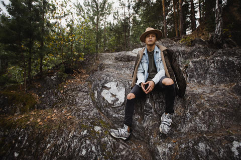 Young man sitting on cliff in forest フォト