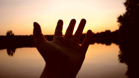 Black silhouette of hand moves it in air, through fingers through rays of sun Footage