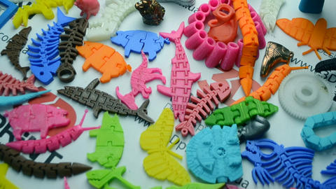Many bright multi-colored objects printed on a 3d printer lie on a flat surface ライブ動画