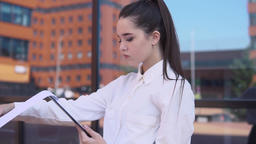 Young business girl stands near business center and looks at working papers Footage