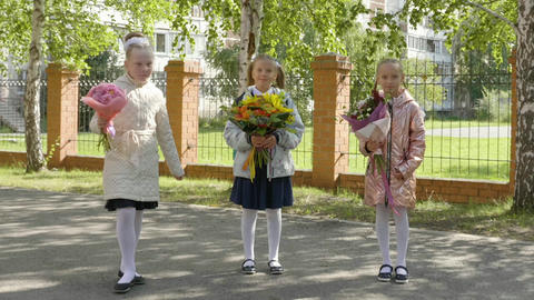 Three happy schoolgirls with flower bouquets going back to school GIF