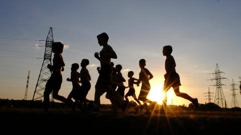 Silhouettes of young boys, jogging on a training against the sunset Footage