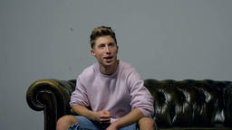Laughter, Thrill, and Excitement by Male Actor on Studio Sofa Footage