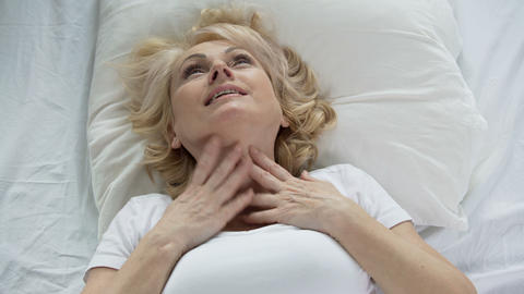 Blond senior woman waking up and touching her face, mask effect, skincare Live Action