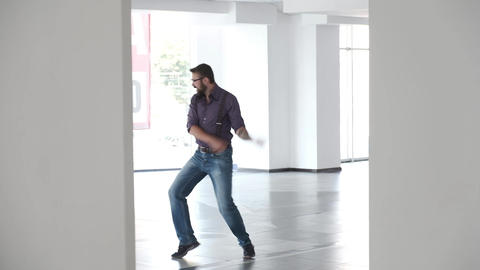 A very excited man is dancing silly in a hall. Then a woman passes and looks Footage