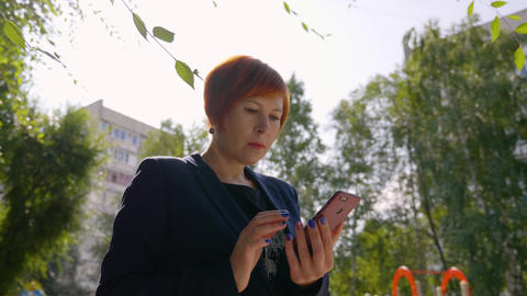 Serious woman with red hair using smartphone outdoors with backlit, low angle Live Action