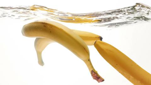 Closeup 4k footage of three yellow bananas falling in water Footage