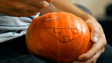 carve a pumpkin for Halloween with a knife Footage