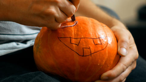 carve a pumpkin for Halloween with a knife Stock Video Footage