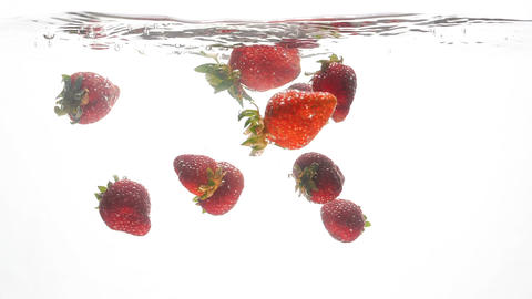 Closeup slow mtoion video of fresh ripe strawberries falling in water against Footage