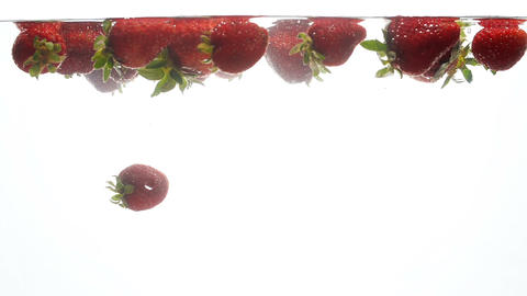 Closeup slow motion footage of ripe strawberries floating on water surface Footage