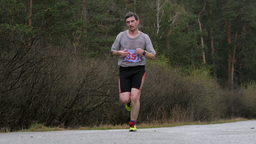 male athlete running on road in woods. slow motion Footage