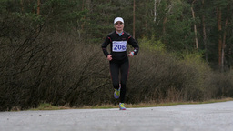 woman athlete running on road in woods. slow motion Footage