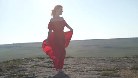 barefoot woman in a flowing dress bounces on the horizon line Footage