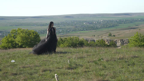 a luxurious woman in a black board walk over the meadow Stock Video Footage