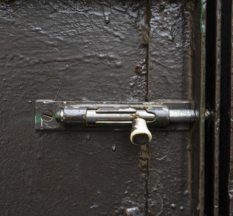 old iron latch on the dark green metal door Photo