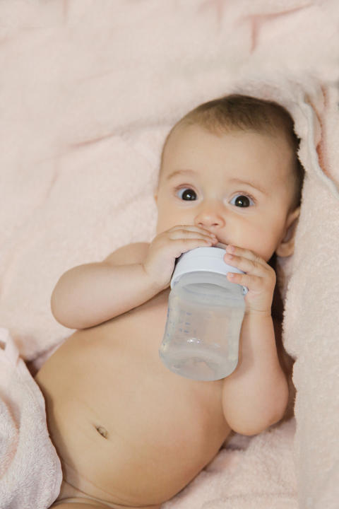 Little baby drinks water from a bottle lying on a blanket フォト