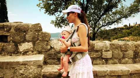 Mom and her child traveling with baby carrier backpack on vacation Footage
