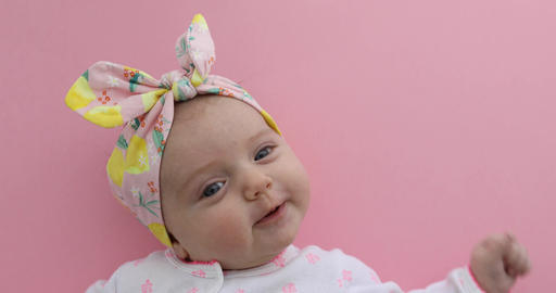 Newborn baby girl smiling pink background Footage