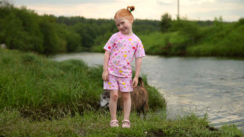 Red-Haired Girl Walking With a Dog on the River. Smile on camera Footage
