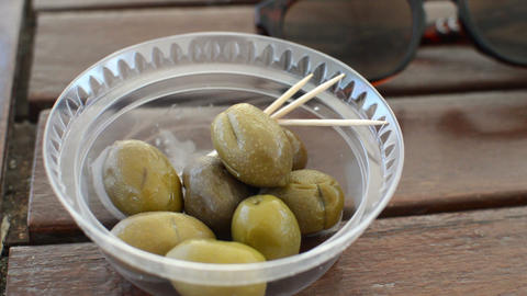 Appetizing green olives in white plate on wooden background. Rustic style Footage