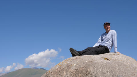 Handsome man sitting on big stone and looking to camera in mountain trip Footage