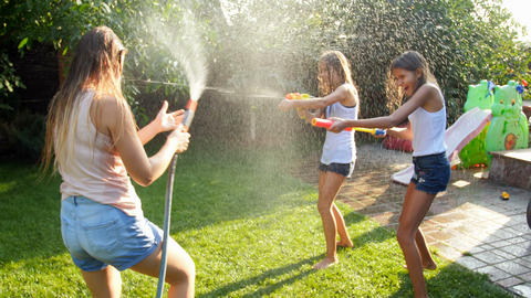 4k video of laughing happy family playing with garden hose and water guns at Footage