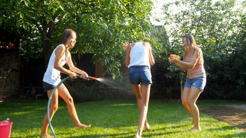 4k video of happy young family having water fight at hot sunny day in garden Footage