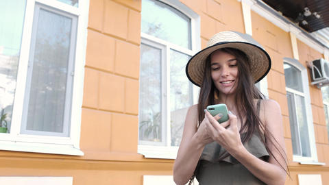 A young woman in a hat and a long dress is texting happily on her phone Footage
