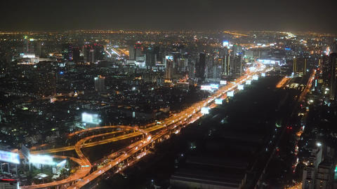 Aerial night illuminated cityscape view of rolling city streets modern buildings Footage