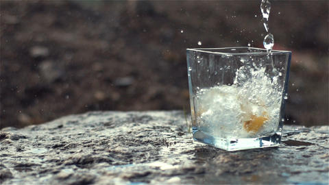 100fps Slow Motion of Sparkling Water and Lemon Falling into Glass Footage