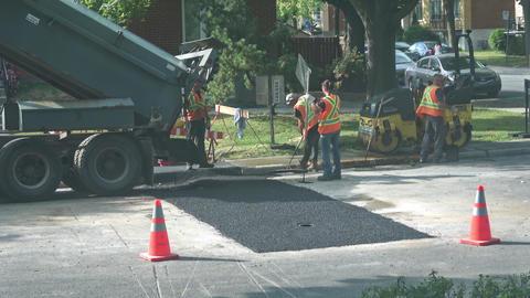 City workers spread asphalt on road Footage