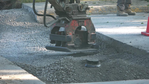 Excavator plate compactor crushes gravel on road with vibrating attachment Footage