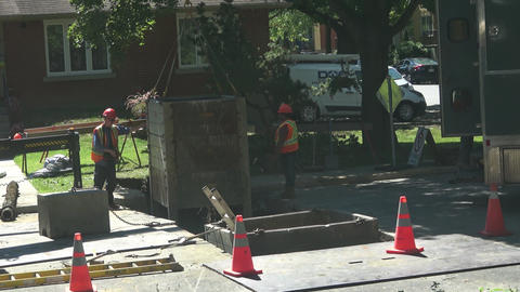 Road crew lowers Trench Box into ground Live Action
