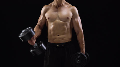 Man flexes his hands with dumbbells, training his biceps on a black background Footage