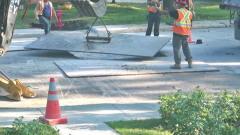 City workers adjust, position steel plate over road with excavated hole in Footage