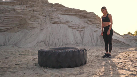 Girl on sand quarry jumping burpee with push-UPS through the wheel in the sand Live Action