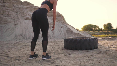 Girl on sand quarry jumping burpee with push-UPS through the wheel in the sand Footage