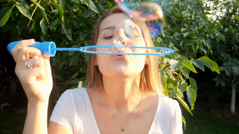 Closeup slow mtoion footage of beautiful young woman blowing soap bubbles in Footage