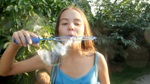 Slow motion video of happy smiling bruntte girl blowing soap bubbles in park at Footage