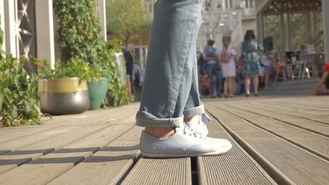 Close-up, female legs in blue slippers, which moves away from the camera, from Live Action