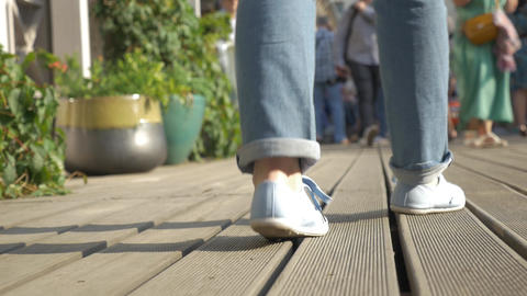 Slow motion, female legs in blue slippers, which moves away from the camera Live Action