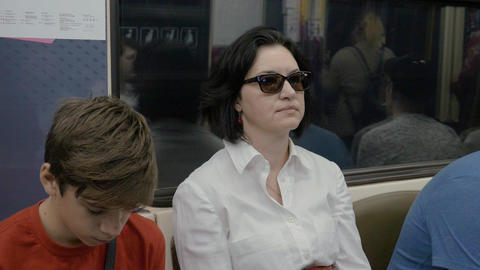 Mother and son ride the train on the subway, in the evening. Son wants to sleep Footage