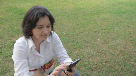 Portrait of a middle-aged woman resting in a clearing, and reads messages on her Live Action