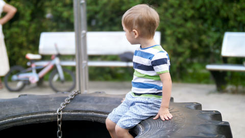 4k video of cute smiling toddler boy sitting on big tire on playground at park Footage