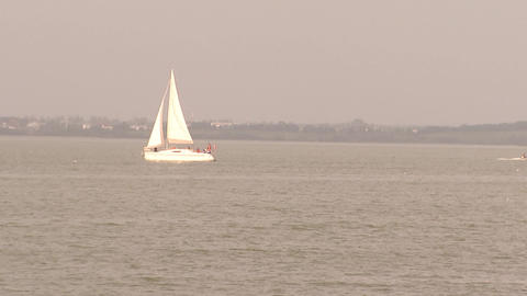 Sailing yacht sailing on the waves of the lake Live Action