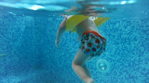 Underwater 4k video of childs' feet in inflatable ring swimming in pool Footage