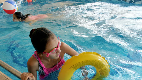 4k video of teenage girl playing and swimming with inflatable ring at swimming Live Action