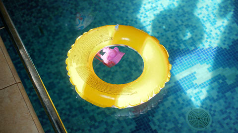 4k video of yellow inflatable ring and plastic toy on water surface at swimming Footage